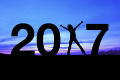 Silhouettieren Sie die junge Frau, die für 2017 neues Jahr glücklich ist Lizenzfreies Stockbild