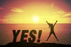 Silhouettieren Sie die junge Frau, die oben Hand wie glückliches Konzept auf Erfolgstext springt und anhebt Stockbild