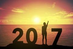 Silhouettieren Sie die junge Frau, die oben ihre Hand über kämpfendes Konzept bei 2017 über einem schönen Sonnenuntergang steht u Lizenzfreie Stockbilder