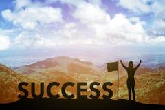 Silhouettieren Sie die junge Frau, die oben ihre Hand über Siegerkonzept bei 2017 über einem schönen Bergblick steht und an anheb Lizenzfreies Stockbild
