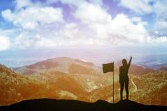 Silhouettieren Sie die junge Frau, die oben ihre Hand über Siegerkonzept bei 2017 über einer schönen Ansicht des Berges steht und Stockbild