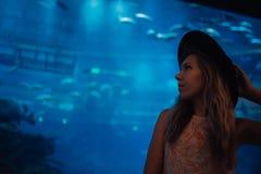 Silhouettieren Sie die jungen hübschen Frauen, die eine moderne Ausstattung im seaquarium tragen Zylinder lizenzfreie stockfotos