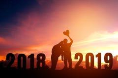 Silhouettieren Sie die jungen Paare, die für 2019 neues Jahr glücklich sind Stockfoto