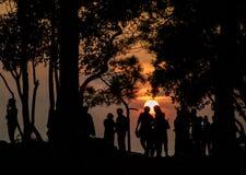 Silhouettieren Sie die Leute, die den Sonnenuntergang auf dem Gipfel aufpassen Stockfotos