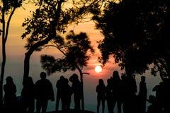 Silhouettieren Sie die Leute, die den Sonnenuntergang auf dem Gipfel aufpassen Stockfotografie