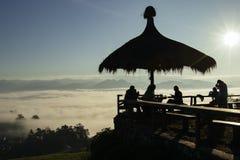 Silhouettieren Sie die Leute, die Sonnenaufgang über einem Wolkenmeer im nort genießen lizenzfreies stockbild