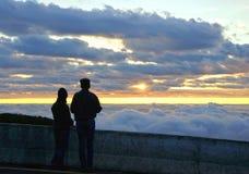 Silhouettieren Sie die Paare, die den schönen Sonnenaufgang auf die Oberseite von betrachten Lizenzfreie Stockbilder