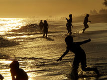 Silhouettieren Sie die Sommerleute, die Spaß bei dem Strandsonnenuntergang haben Stockbild