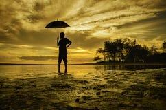 Silhouettieren Sie eine Jungenstellung und betrachten Sie die Rückseite beim Halten eines Regenschirmes Lizenzfreies Stockfoto