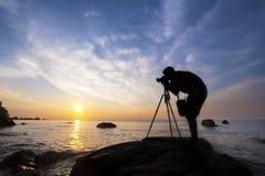 Silhouettieren Sie einen Fotografen, der Fotos des Sonnenaufgangs auf einem Felsen macht, Lizenzfreies Stockbild