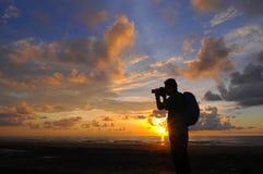 Silhouettieren Sie einen Fotografen, der Fotos des Sonnenaufgangs auf einem Felsen macht, Stockfoto