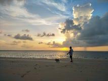 Silhouettieren Sie einen Mann und Dong gehen auf den Strand Stockfoto
