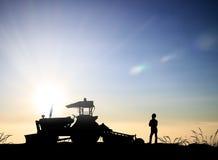 Silhouettieren Sie Erntemaschine auf einem Bauernhof, der mit Gemüse gepflanzt wird, Stockfoto