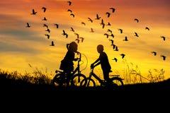 Silhouettieren Sie Fahrradblick des kleinen Jungen und des kleinen Mädchens Reitzur Menge wenigen pfeifenden Entenfliegens auf So lizenzfreie stockfotografie