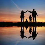 Silhouettieren Sie Familienhaus auf Sonnenuntergang