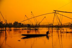 Silhouettieren Sie Fischer auf dem Boot, das indem Sie traditionelle Netz-FI fischt, verwenden Lizenzfreie Stockbilder