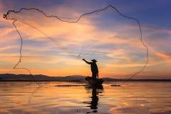 Silhouettieren Sie Fischer auf Fischerbooteinstellungsnetz mit Sonnenaufgang stockfotos