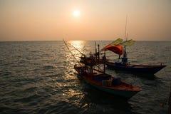 Silhouettieren Sie Fischer ` s Boote im Meer Stockfotografie