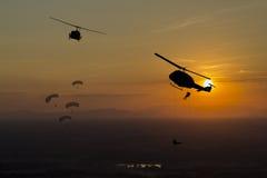 Silhouettieren Sie Flugzeug, Hubschrauber und Fallschirm bei Sonnenuntergang Lizenzfreie Stockfotos