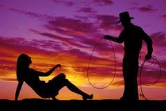 Silhouettieren Sie Frau im Kleid und Fersen betrachten oben Cowboy Stockbild