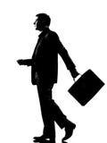Silhouettieren Sie gehendes Profil des Mannes mit Aktenkoffer Stockfoto