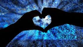 Silhouettieren Sie Hände in der Herzform und Papiere während eines Konzerts stockbild