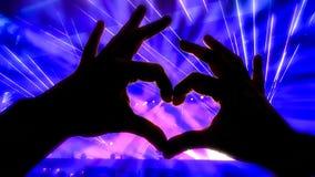 Silhouettieren Sie Hände in der Herzform während eines Konzerts stockfotos