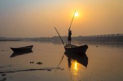 Silhouettieren Sie hölzernes Boot mit Ruderer bei Sonnenuntergang auf Fluss Damodar Stockfotografie