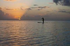Silhouettieren Sie herein vom Paddelinternatsschüler im Pazifischen Ozean lizenzfreies stockbild
