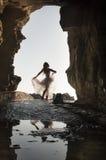 Silhouettieren Sie junge schöne Braut im Felsentorbogen am Strand stockbild