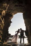 Silhouettieren Sie junge schöne Brautpaare im Felsentorbogen am Strand stockbild