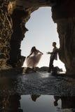 Silhouettieren Sie junge schöne Brautpaare im Felsentorbogen am Strand stockfoto