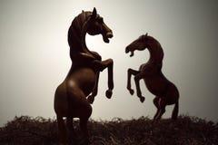 Silhouettieren Sie kämpfende Pferde im archivierten Gras, die hölzerne Pferdeskulptur auf weißem Hintergrund Stockbild