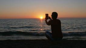 Silhouettieren Sie Mann mit der digitalen Tablette, die Foto am Sonnenuntergangstrand macht Die Sonne wird fast hinter den Ozean  stock video
