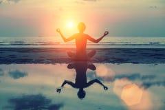 Silhouettieren Sie Meditationsmädchen auf dem Hintergrund des erstaunlichen Meeres und des Sonnenuntergangs Stockbilder
