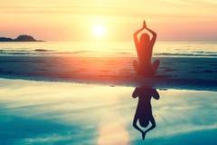 Silhouettieren Sie Meditationsmädchen auf dem Hintergrund des erstaunlichen Meeres und des Sonnenuntergangs Stockfotos