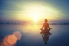 Silhouettieren Sie Meditationsyogafrau auf dem Hintergrund des Meeres und des erstaunlichen Sonnenuntergangs Stockfotografie