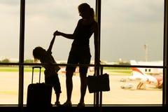 Silhouettieren Sie Mutter mit ihrem Sohn, der am Fenster in der Luft steht Stockbild