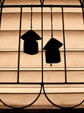 Silhouettieren Sie Paare der keramischen Windglocke auf Fenster Lizenzfreies Stockfoto