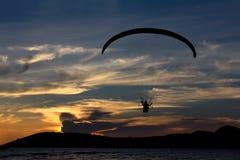 Silhouettieren Sie paramotor/Gleitschirmfliegen auf dem Himmel mit seavie Stockfoto