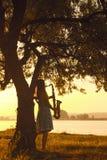 Silhouettieren Sie Porträt der schönen jungen Frau nahe dem Stamm eines Baums bei Sonnenaufgang mit Saxophon Lizenzfreies Stockfoto