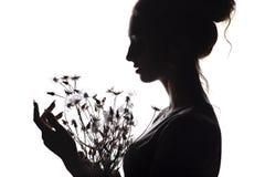 Silhouettieren Sie Porträt eines schönen Mädchens mit einem Blumenstrauß des Löwenzahns, Gesichtsfrauenprofil auf einem Weiß loka stockbilder