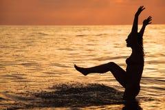 Silhouettieren Sie schönes Frauenspiel im Meer im Abend Stockfotos