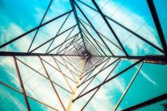 Silhouettieren Sie Schuss von Strommasten mit bewölktem Himmel Stockfotos