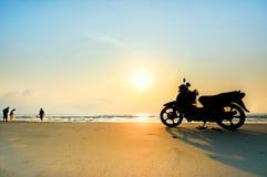 Silhouettieren Sie Stände eines Motorrads auf dem Strand Stockbild
