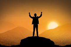 Silhouettieren Sie stehende Spitze des Geschäftsmannes des Berges Stockfoto
