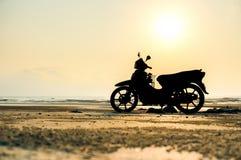 Silhouettieren Sie Stände eines Motorrads auf dem Strand Lizenzfreie Stockbilder