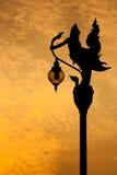 Silhouettieren Sie thailändischen Kunststatuenlaternenpfahl am Abend Stockbilder