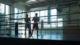 Silhouettieren Sie Trainingssparring von zwei Boxern auf einem Ring