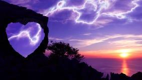 Silhouettieren Sie Valentinsgrußhintergrundkonzept, Herz-förmigen Stein auf einem Berg Stockfotografie